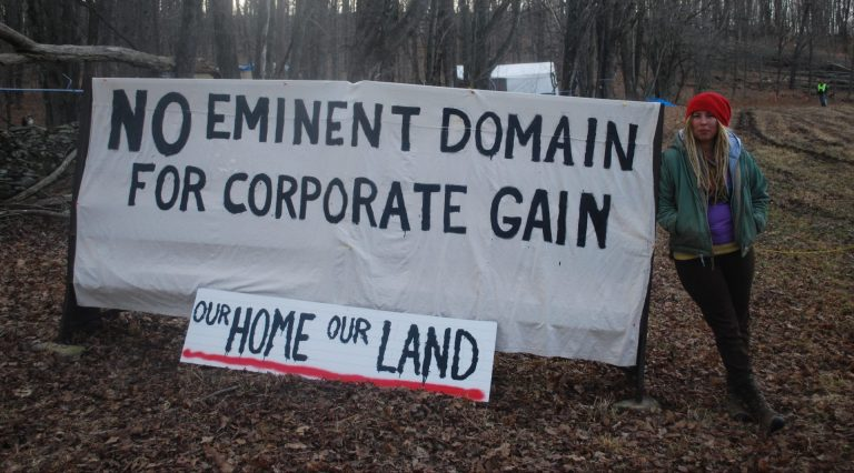 Megan Holleran stands by a sign on her family's land. The Hollerans lost their court battle to save their maple trees from eminent domain seizure. The trees are being cut to make way for the new Constitution Pipeline, which has been stalled amid legal battles. (Jon Hurdle/StateImpact Pennsylvania)