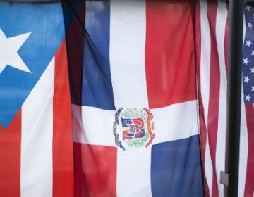 The flags of Puerto Rico, Dominican Republic and the United States hang in the window of the Latino Hispanic American Community Center in Harrisburg. (Tom Downing/WITF)