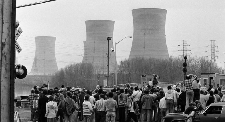 Newsmen and spectators stand in front of the main gate of the Three Mile Island Nuclear Generating Station in Middletown, Penn., April 2, 1979. (Jack Kanthal/The Associated Press)