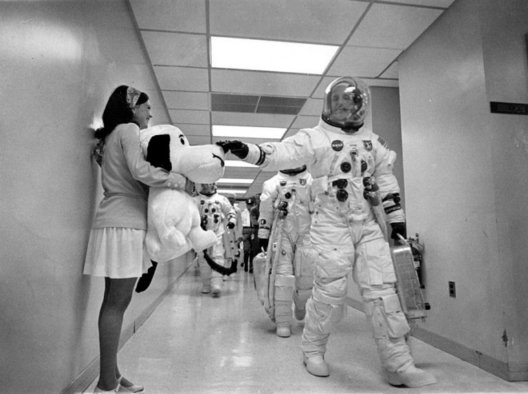 As the Apollo 10 crew walks along a corridor on the way to Launch Complex 39B, mission commander Thomas P. Stafford pats the nose of Snoopy, the mission's mascot, held by Jamye Flowers, astronaut Gordon Coopers' secretary. (NASA)