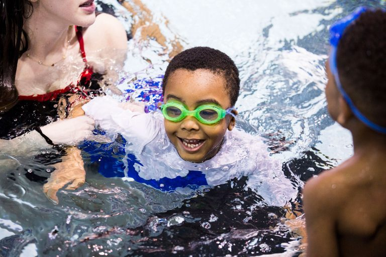 Natalie Edman (left), a freshman at the University of Pennsylvania, gives Quintin Whitner, 6 (center), a swimming lesson through We Can Swim on March 23, 2019. (Rachel Wisniewski for WHYY)