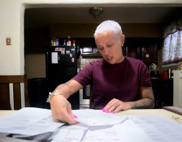 At the kitchen table, Summer Mills goes over documents accumulated in the past months while dealing with dental issues on April 12, 2019. (Bastiaan Slabbers for WHYY)