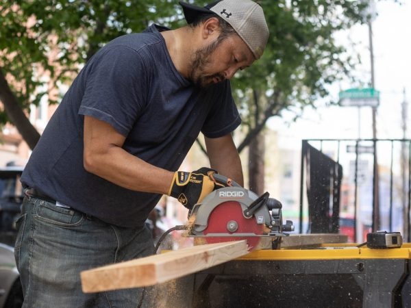 Kevin Lally cuts lumber for custom-sized garden beds. (Angela Gervasi for WHYY)