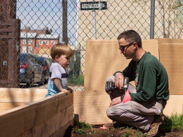 Clifford Brown (right), a former volunteer with La Finquita, stops to chat with Sam Prasak as the new community garden progresses. (Angela Gervasi for WHYY)
