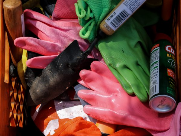 Gloves, gardening tools and insect repellent await volunteers at a new garden on Jefferson and Orkney streets in Kensington. (Angela Gervasi for WHYY)