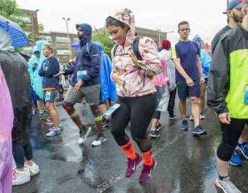 While waiting for the Broad Street Run to begin, Alba Miranda warms up near the Olney Transportation Center. Miranda is a member of the running group Latinas in Motion. (Jonathan Wilson for WHYY)