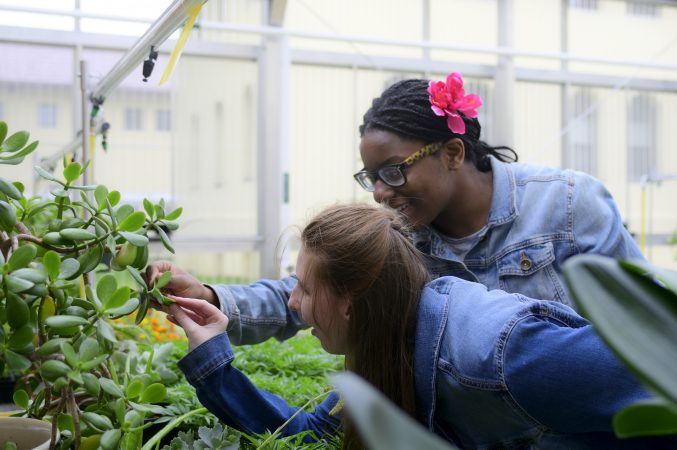 Ashlee Preston, 19 and Shamirah Brown, 18 explore plants at the new horticulture center for students who are blind, visually impaired or have other disabilities at the Overbrook School of the Blind, on Tuesday. (Bastiaan Slabbers for WHYY)