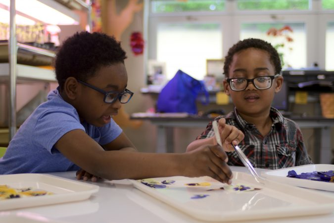 Pre-schoolers Sean and Ari prepare pressed flowers for cards at the classroom of the new horticulture center for students who are blind, visually impaired or have other disabilities at the Overbrook School of the Blind, on Tuesday. (Bastiaan Slabbers for WHYY)