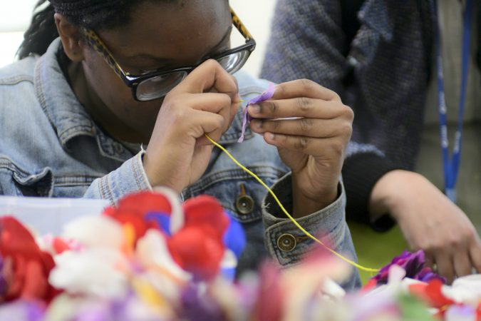 Shamirah Brown, 18, strings together (fake) flowers to be used as decoration for the opening of new horticulture center for students who are blind, visually impaired or have other disabilities at the Overbrook School of the Blind, on Tuesday. (Bastiaan Slabbers for WHYY)