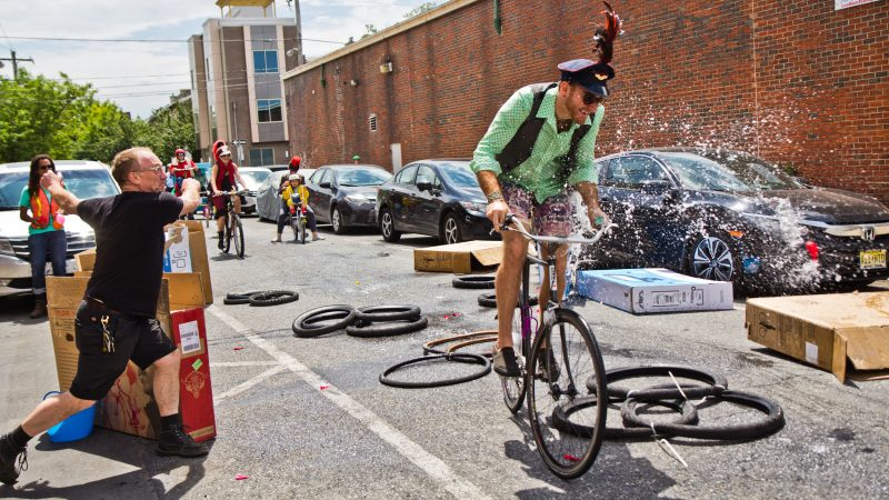 Riders get pelted with water balloons at Transport Cycles on the route of the Kensington Kinetic Sculpture Derby. (Kimberly Paynter/WHYY)