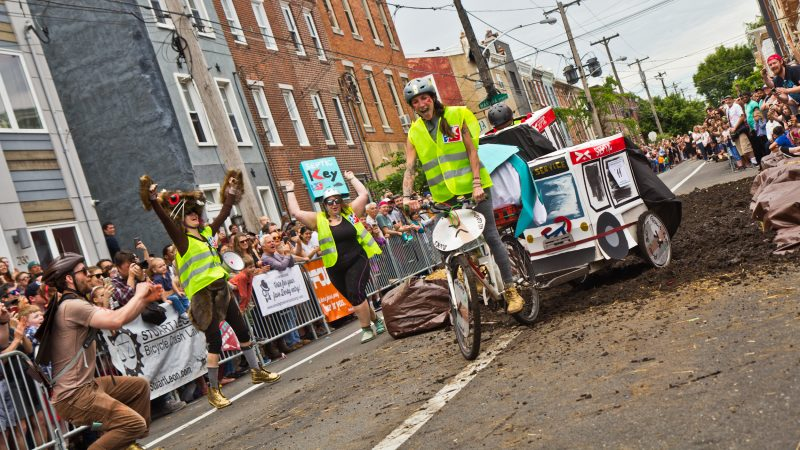 The Crazy Bike Clan celebrates as their accordion bus makes it through the mud pit. (Kimberly Paynter/WHYY)