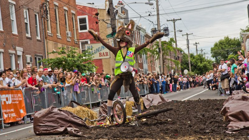 CB, lead costume designer for the Crazy Bike Clan, celebrates by throwing mud in the air. (Kimberly Paynter/WHYY)