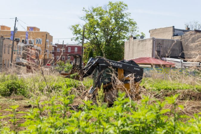 Anthony Patrick clears a plot of land near the César Andreu Iglesias Community Garden near Lawrence and Norris streets. (Angela Gervasi for WHYY)