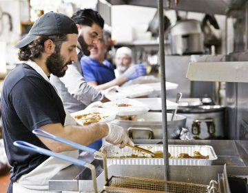 (From left) Anas Dabbour, Abbulah Ibrahim, and Munir Odeh work in an assembly line to create boxes of fish, chicken, and lamb dinners at the Al Amana Grocery on May 20, 2019. Dabbour's family established the grocery in 1993, after emigrating from Syria in 1992. (Rachel Wisniewski for WHYY)