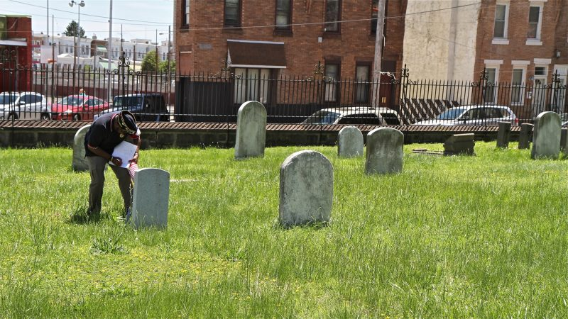 Darryrl Johnson, commander of American Legion Latin American Post 840, checks a list Civil War and Mexican American War veterans buried in St. Anne's Cemetery in order to place American flags on their graves for Memorial Day. (Ximena Conde/WHYY)