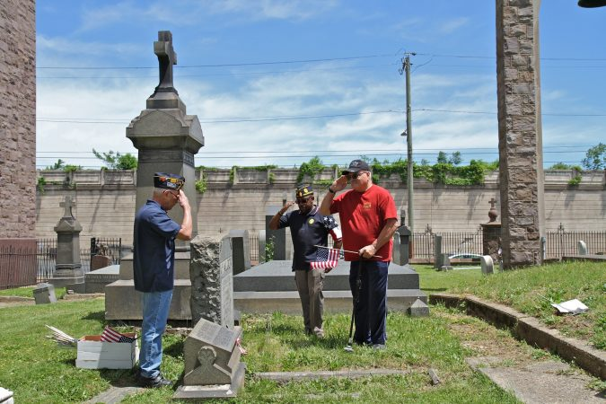 Members of American Legion Latin American Post 840 in North Philadelphia (from left) José Rivera, Darryrl Johnson and José Vargas, plant flags at the graves of veterans in St. Anne's Cemetery. (Ximena Conde/WHYY)