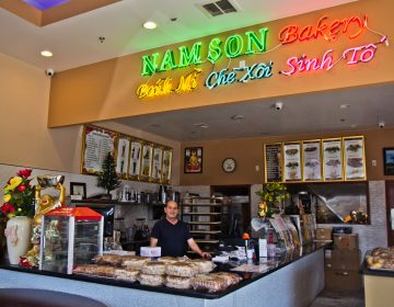 The owner of Nam Son Bakery behind the counter of the South Philadelphia shop. (Kimberly Paynter/WHYY)
