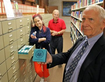 Norval Reece, treasurer of the board of trustees of the David Library, holds a box of mircofim from the collection, which contains about a million pages of original material from the Revolutionary War era preserved on microfilm. He is joined by chief operating officer Meg McSweeney and acting librarian Andrew Zellers-Frederick. (Emma Lee/WHYY)