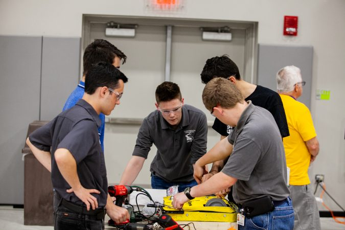 Students from Upper Bucks County Technical School work on their robot Pre-Swiss Cheese between rounds at the Liberty Bots competition Saturday at Montgomery County Community College. (Brad Larrison for WHYY)
