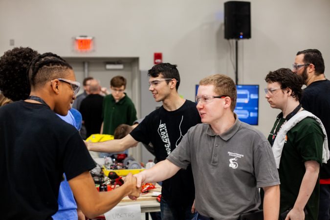 Students from Upper Bucks County Technical School and MaST Community Charter School shake hands after a round of competition in the Liberty Bots competiton Saturday at Montgomery County Community College. (Brad Larrison for WHYY)