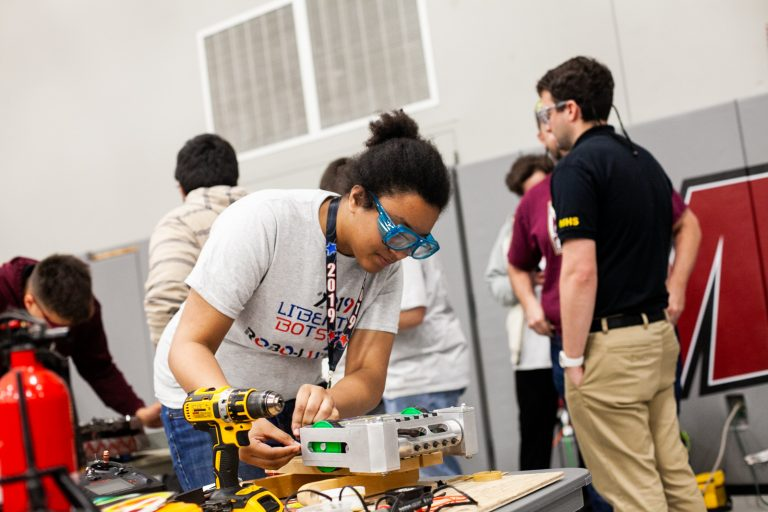 Ashley Yates of Harry S. Truman High School works on her team's robot between rounds at the Liberty Bots competition Saturday at Montgomery County Community College. (Brad Larrison for WHYY)
