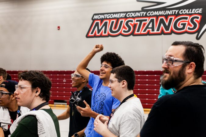 Students from MaST Community Charter School celebrate a victory over Trenton High School Saturday during the Liberty Bots competition Montgomery County Community College. (Brad Larrison for WHYY)