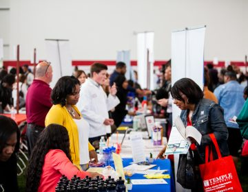 Job seeking Philadelphians spoke with employers from around the region Thursday morning at the 13th annual Neighborhood Job Fair at Temple University. (Brad Larrison for WHYY)
