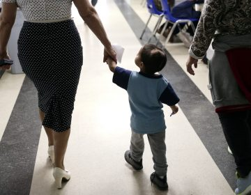 In this Friday, Jan. 11, 2019, photo, Maria Orbelina Cortez, (right), walks with her 3-year-old son, Julio, (center), and a worker at the Catholic Charities shelter in McAllen, Texas. Orbelina says she decided to flee El Salvador after her husband attacked her and caused a pan of hot oil to fall, scalding Julio and leaving a scar on his head. (Eric Gay/AP Photo)