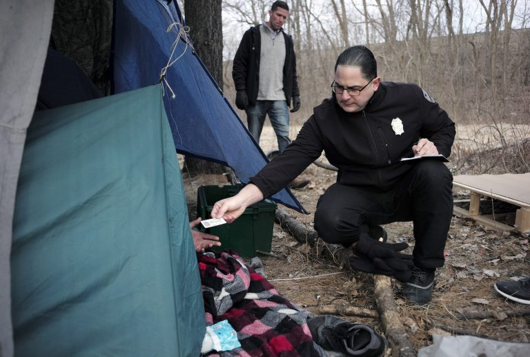In this Tuesday, Feb. 12, 2019 photo Worcester Police officer Angel Rivera, right, returns a license to an unidentified man as Rivera asks if he has been tested for Hepatitis A at the entrance to a tent where the man spent the night in a wooded area, in Worcester, Mass. (Steven Senne/AP Photo)