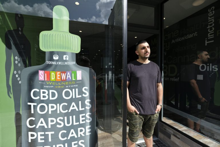 In this photo taken Thursday, March 21, 2019, Gus Dabais stands outside his Sidewalk Wellness store in San Francisco. CBD oil-infused food, drinks and dietary supplements are popular even though the U.S. government says they're illegal and some local authorities have forced retailers to pull products. The confusion has California, Texas and other states moving to legalize the cannabis compound that many see as beneficial to their health. (Eric Risberg/AP Photo)