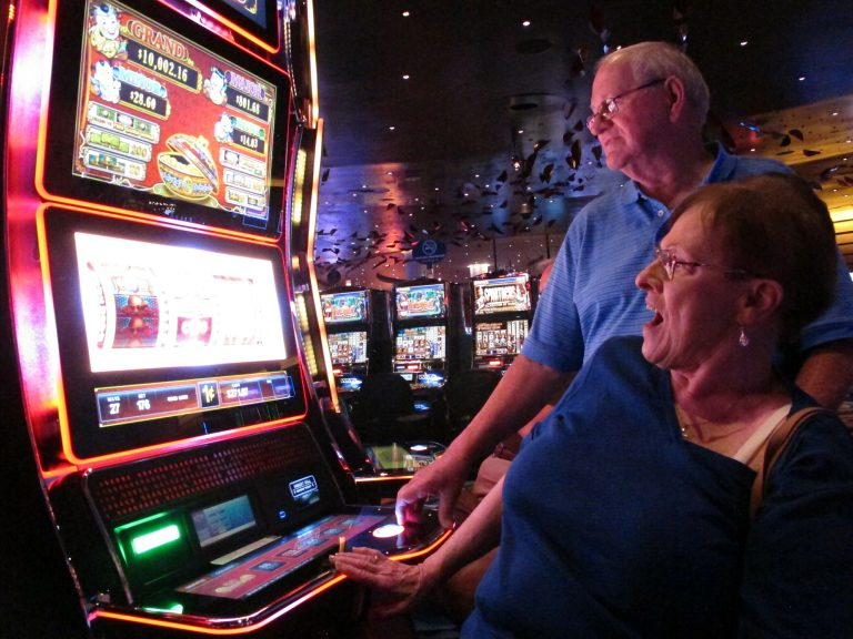 In this June 25, 2018 photo, Joyce Green of Vineland, N.J. reacts to a winning spin at a slot machine as her husband Tom looks on inside the Ocean Casino Resort in Atlantic City, N.J. The casino formerly known as Revel will turn a profit in May after months of steep losses. (Wayne Parry/AP Photo)