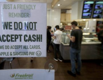 This Thursday, May 2, 2019, photo shows a sign posted on a door alerting customers that cash is not accepted at Freshroll Vietnamese Rolls and Bowls in San Francisco. San Francisco now requires brick-and-mortar retailers to take cash in payment for goods, joining Philadelphia and New Jersey in banning a practice that critics say discriminates against the poor. (Jeff Chiu/AP Photo)
