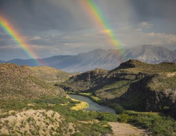 This December, 2017 photo released by Fin and Fur Films shows a double rainbow over Big Bend National Park, Texas, and the Rio Grande along the U.S.-Mexico border, with Mexico being on the right side of the river. The new documentary,