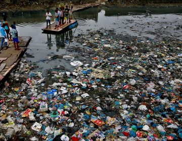 In this Sunday, Oct. 2, 2016 file photo, a man guides a raft through a polluted canal littered with plastic bags and other garbage in Mumbai, India. United Nations officials say nearly all of the world's countries have agreed on a deal to better manage plastic waste, with the United States a notable exception. A