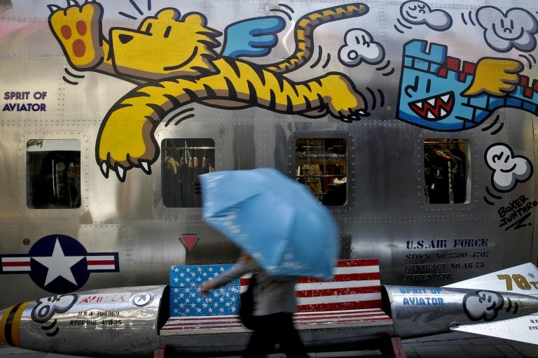 A woman walks by a bench painted with an American flag outside a fashion boutique selling U.S. brand clothing at the capital city's popular shopping mall in Beijing, Monday, May 13, 2019.  Companies waited Monday to see how China decides to retaliate for President Donald Trump's latest tariff hike while forecasters warned their escalating fight over technology and trade might disrupt a Chinese economic recovery. (Andy Wong/AP Photo)