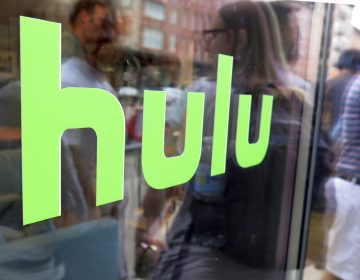 This June 27, 2015, file photo, shows the Hulu logo on a window at the Milk Studios space in New York. Disney has struck a deal with Comcast that gives it full control of streaming service Hulu. The companies said Tuesday, May 14, 2019, that as early as January 2024 Comcast can require Disney to buy NBCUniversal's 33% interest in Hulu and Disney can require NBCUniversal to sell that stake to Disney for its fair market value at that future time. (Dan Goodman/AP Photo)