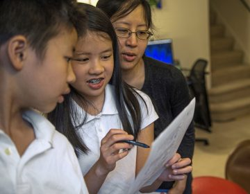 Vivian Loh, (center), a seventh grader at Winchester Thurston School and the first girl to win the Pennsylvania MATHCOUNTS competition, explains the solution to a math problem to her brother Vincent, 10, and their mother Debbie after they each completed a practice worksheet in the morning before school, Thursday, April 25, 2019, at their home in Squirrel Hill.  (Alexandra Wimley/Pittsburgh Post-Gazette via AP)
