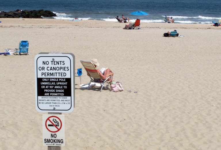 In this Monday, May 20, 2019 photo, beachgoers sit on the sand beyond a sign indicating that smoking is prohibited on the beach in Spring Lake, N.J. A statewide smoking ban is in effect at New Jersey's beaches for the start of the 2019 summer season, although towns can set aside up to 15% as smoking sections. (Wayne Parry/AP Photo)