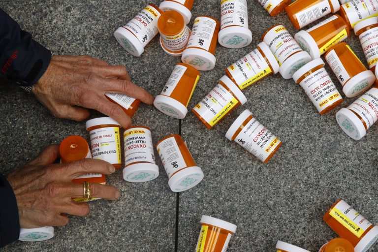 In this Friday, April 5, 2019, file photo, a protester gathers containers that look like OxyContin bottles at an anti-opioid demonstration in front of the U.S. Department of Health and Human Services headquarters in Washington, D.C. (Patrick Semansky/AP Photo)