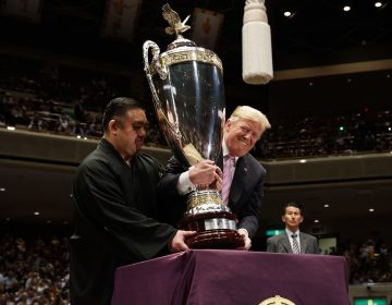 President Donald Trump picks up the 'President's Cup' to present to the Tokyo Grand Sumo Tournament winner Asanoyama, at Ryogoku Kokugikan Stadium, Sunday, May 26, 2019, in Tokyo. (Evan Vucci/AP Photo)