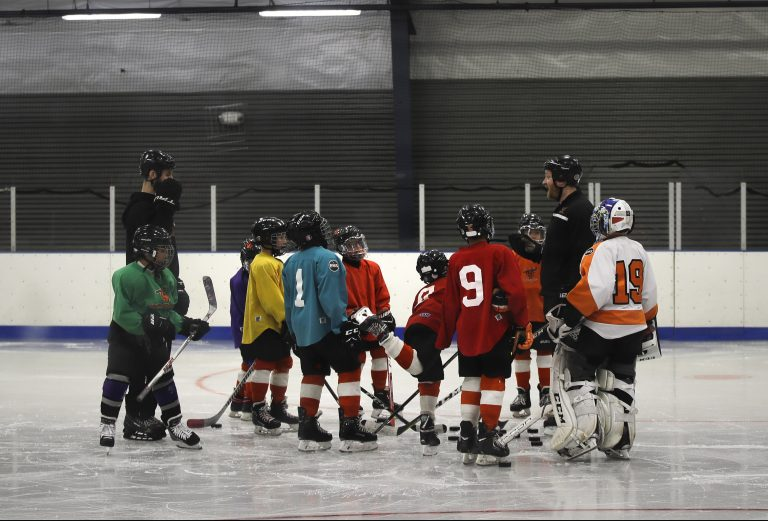 FILE - In this Feb. 21, 2019, file photo, Malakye Johnson (1) gathers with his teammates during a Snider Hockey practice at the Scanlon Ice Rink in Philadelphia. The Philadelphia-based Snider Hockey organization named after the late Flyers owner now has over 3,000 kids in its program and almost a third are girls. Snider Hockey officials want to get to a point that boys and girls are split 50-50, and a new endeavor with the Howe Foundation is another step toward that goal. (AP Photo/Matt Rourke, File)