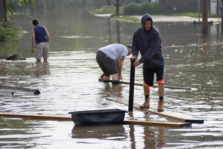 Workers wade through floodwaters to recover lumber that floated from a lumber yard, Wednesday, May 29, 2019, in Harmony, Pa. More storms are predicted for the area. (AP Photo/Keith Srakocic)