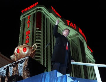 Donald Trump ascends the stairs with his fist raised from the genie's lamp after opening the Trump Taj Mahal Casino Resort in a spectacular show of fireworks and laser lights Thursday evening in Atlantic City, N.J., on April 5, 1990.  Behind Trump is the 42-story hotel.  (AP Photo/Chaarles Rex Arbogast)