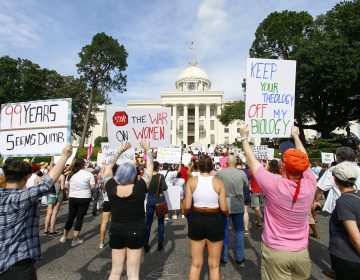 Protesters for women's rights hold a rally on the Alabama Capitol steps to protest a law passed last week making abortion a felony in nearly all cases with no exceptions for cases of rape or incest, Sunday, May 19, 2019, in Montgomery, Ala. (AP Photo/Butch Dill)