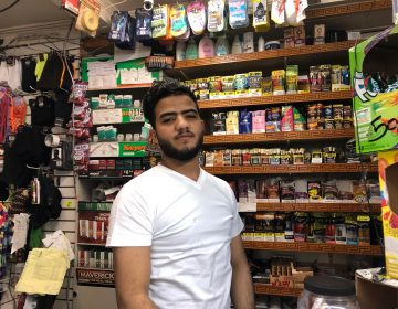 Nasraddin Asramat, who runs the cash register at Bill's Deli Market, said crowds have thinned since the store resumed business. (Cris Barrish/WHYY)