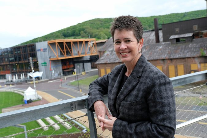ArtsQuest President and CEO Kassie Hilgert stands on the SteelStacks campus, which sits at the base of the former blast furnaces of Bethlehem Steel. (Matt Smith for Keystone Crossroads)