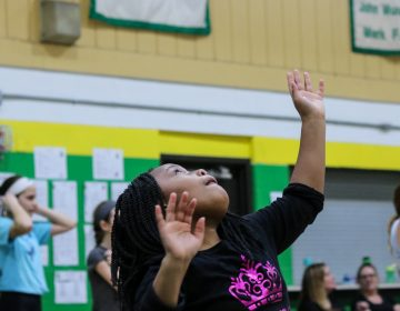 Faith Green practices setting volleyballs at a sports clinic through Philly Girls in Motion. (Angela Gervasi for WHYY)