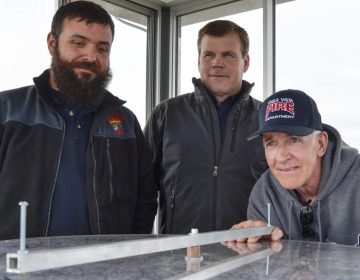 Officials from the Moshannon Forest District gather around the alidade, an instrument used to help personnel staffing lookout towers pinpoint the location of wildfires. From left to right, Joe Polaski, John Hecker and Larry Bickel stand in the new Chestnut Ridge tower. (Amy Sisk / StateImpact Pennsylvania)