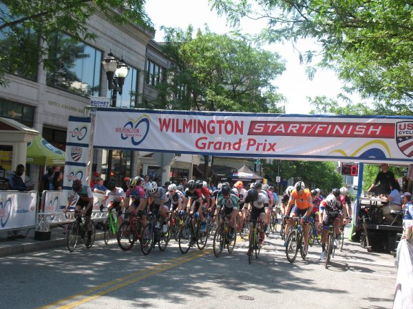 Cyclists cross the starting line during the Wilmington Grand Prix on Saturday (John Mussoni/WHYY)