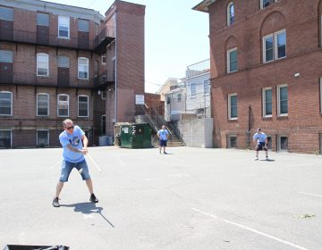 Two teams battle it out to advance to the next round of the 10th Annual John Marzano Half Ball Tournament. (Ximena Conde/WHYY)